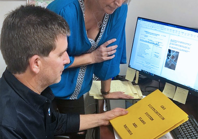 photo of a woman and man reviewing pipeline inspection services manuals and plans
